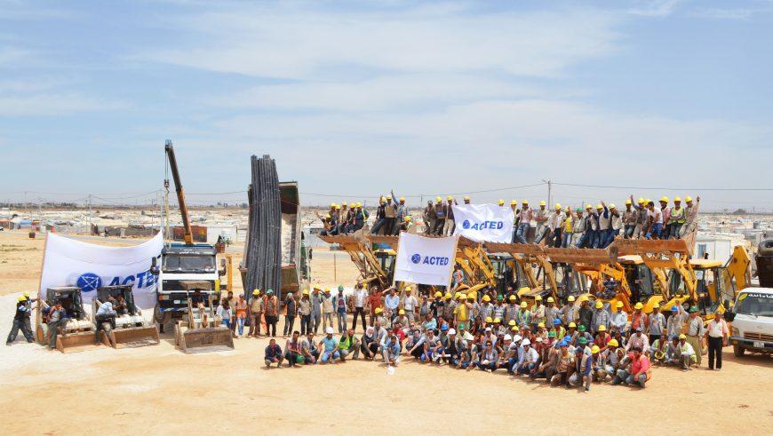 Les travailleurs syriens et le personnel d'ACTED célèbrent l'achèvement de la phase 1 du réseau d'assainissement, Zaatari