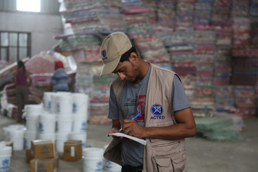 ACTED field staff checks supplies of distribution materials.
