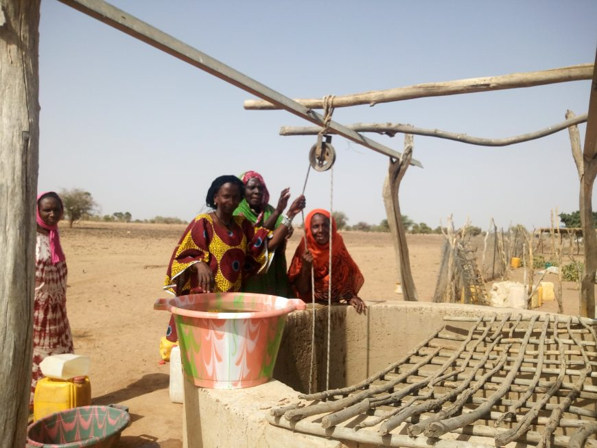 Senegalese women stand next to water well