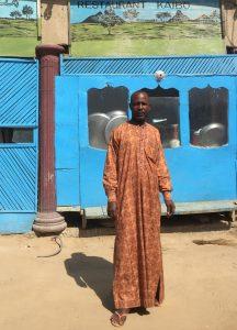 un jeune homme bénéficiaire du soutien d'ACTED devant son stand de chaussures sur un marché local de la capitale